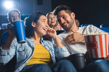 Happy multicultural couple with popcorn watching movie together in cinema stock vector