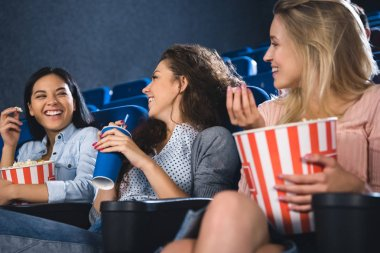 happy multiracial women with popcorn watching film together in movie theater