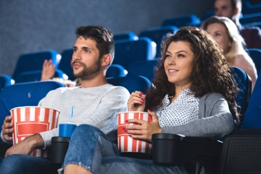Couple with popcorn and soda drink watching film together in cinema stock vector