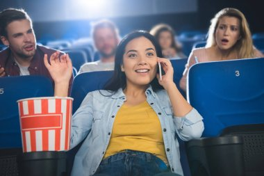 Asian woman talking on smartphone while watching movie in cinema stock vector