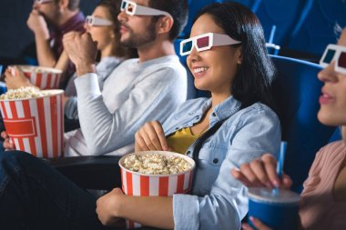 smiling multiethnic friends in 3d glasses with popcorn watching film together in movie theater