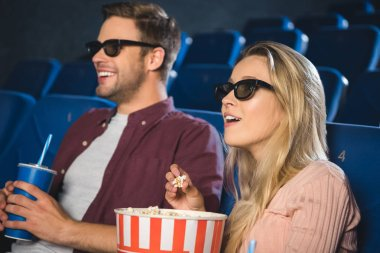 Emotional couple in 3d glasses with popcorn and soda drink watching film together in cinema stock vector