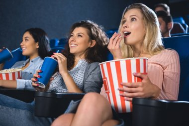 emotional multiracial women with popcorn watching film together in movie theater