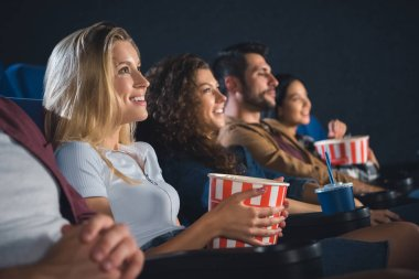 smiling multiethnic friends with popcorn watching film together in movie theater