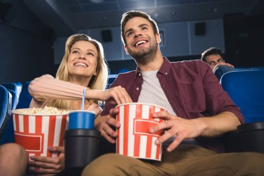 Happy couple with popcorn and soda drink watching film together in cinema stock vector