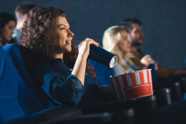 side view of woman with soda drink and popcorn watching movie in cinema