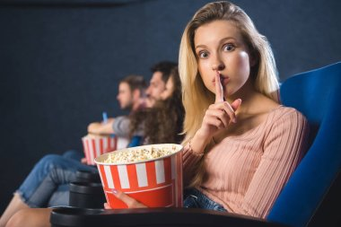 selective focus of woman with popcorn showing silence sign in cinema