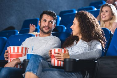 couple with popcorn and soda drink watching film together in cinema