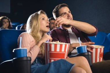 Emotional couple with popcorn watching film together in cinema stock vector