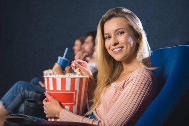 Selective focus of smiling woman with popcorn in cinema stock vector
