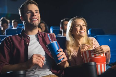 cheerful couple with popcorn and soda drink watching film together in cinema