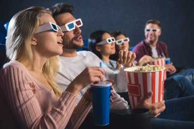 multiethnic friends in 3d glasses with popcorn watching film together in movie theater