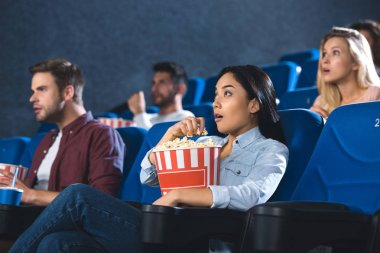 Shocked asian woman with popcorn watching movie in cinema alone stock vector