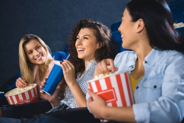 cheerful multiracial women with popcorn watching film together in movie theater