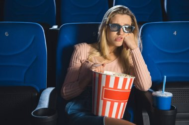 portrait of bored woman in 3d glasses with popcorn watching film alone in cinema