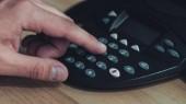 Fotografie Oříznout záběr lidstva mačkání tlačítka konferenční telefon na dřevěný stůl