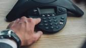 Fotografie Oříznout záběr podnikatel s stylové hodinky tlačí tlačítko konferenční telefon na stole v kanceláři