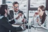 Skupina podnikatelů s kontrakty mají schůzku v moderní kanceláři