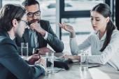 Fotografia gente di affari sicura seduti attorno telefono da conferenza presso ufficio moderno