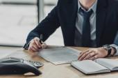 Schnappschuss von Geschäftsmann bei Vertragsunterzeichnung am Wochentag