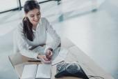 Fotografie Erhöhte Ansicht des jungen glücklich geschäftsfrau Papierkram zu tun und reden von Konferenztelefon auf Tisch im Büro