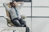 pohledný podnikatel relaxační na luxusní křeslo v moderní kanceláři