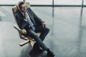 high angle view of handsome happy businessman sitting on luxury armchair at modern office