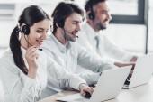 Fotografie lächelnd Call Centermanager in weißen Hemden gemeinsam sitzen hintereinander im modernen Büro