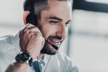 happy adult support hotline worker with microphone at work