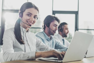happy call center managers working with laptops and microphones at modern office