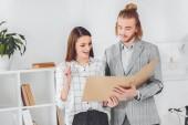 Fotografie businesswoman showing idea gesture when looking at documents in folder