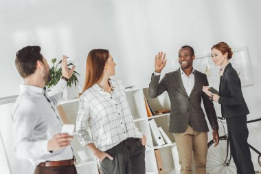 smiling multicultural businesspeople waving hands in office
