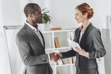 african american businessman and caucasian businesswoman shaking hands