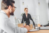 Fotografie podnikatelka v formálním obleku, stojící proti tabulky a mluví k týmu na kancelářské prostory