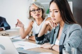 irritated businesswoman gesturing and talking to colleague in office