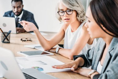 multiethnic businesswomen talking about project in office