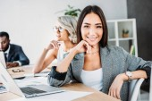 smiling attractive asian businesswoman looking at camera in office