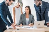 mladí multikulturní podnikatelé stojící kolem vedoucí týmu a při pohledu na dokumenty