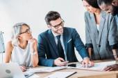 Multikulturelle Geschäftsleute arbeiten im Büro an einem Projekt und stehen mit Dokumenten am Tisch