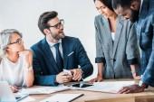 mladí multikulturní podnikatelé pracující na projektu v úřadu