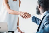 Photo cropped image of multiethnic businesspeople shaking hands in office