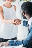 Fotografie cropped image of multicultural businesspeople shaking hands in office