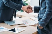 Photo cropped image of multicultural businessmen shaking hands in office