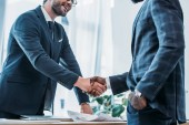 oříznutý obraz úsměvu multikulturní podnikatelé potřesení rukou v úřadu