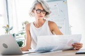 beautiful caucasian businesswoman reading documents in office