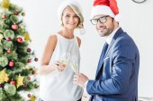 Fotografie smiling businesspeople in santa hats clinking with glasses of champagne in office