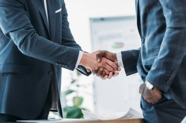 cropped image of multicultural businessmen in suits shaking hands in office