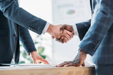 cropped image of multiethnic businessmen shaking hands in office