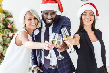 smiling multicultural businesspeople in santa hats clinking with glasses of champagne in office