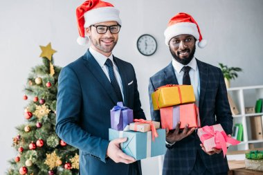 smiling multicultural businessmen in santa hats holding gift boxes in office and looking at camera